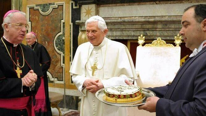 Michael J. Bransfield (i) presenta una tarta de cumpleaños al Papa Benedicto XVI