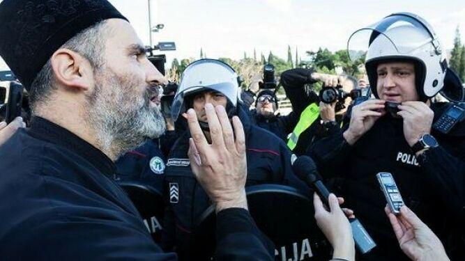 Un sacerdote de la Iglesia Ortodoxa Serbia habla con un policía antidisturbios en un puente cerca del parlamento, antes de votar el proyecto de ley sobre 'Libertades religiosas y derechos legales de las organizaciones religiosas' en Podgorica