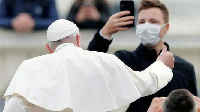 El Papa saluda a un fiel que le graba con una mascarilla puesta