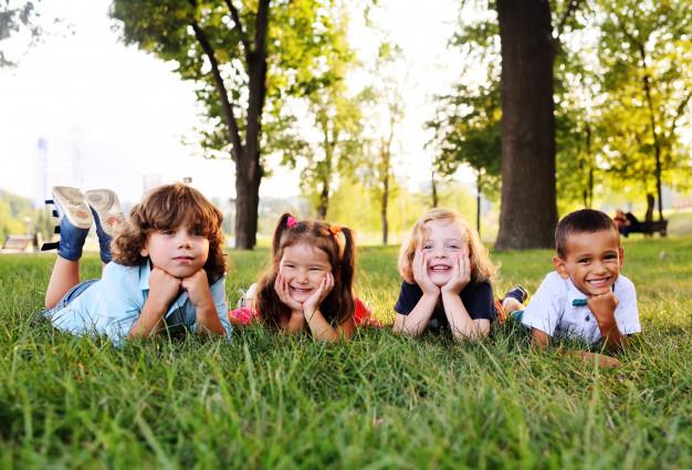 grupo-ninos-edad-preescolar-jugando-parque-hierba_74906-1413