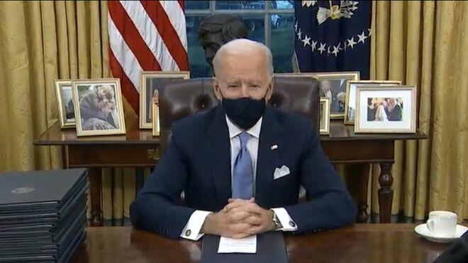 Biden, en el Despacho Oval. A su izquierda, la fotografía con el Papa Francisco