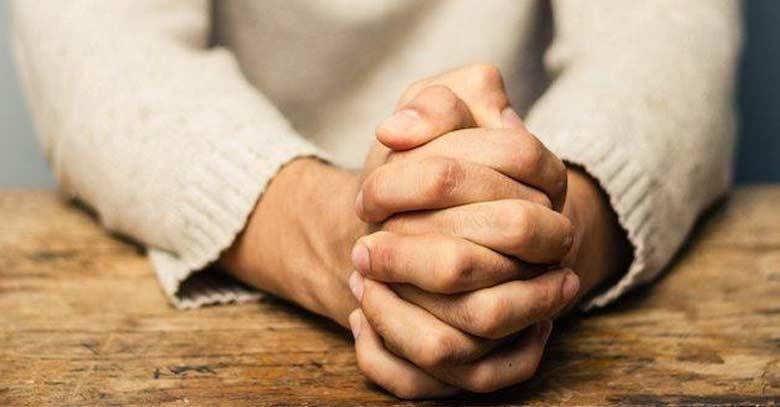 manos-de-hombre-juntas-rezando-sobre-tabla-de-mesa